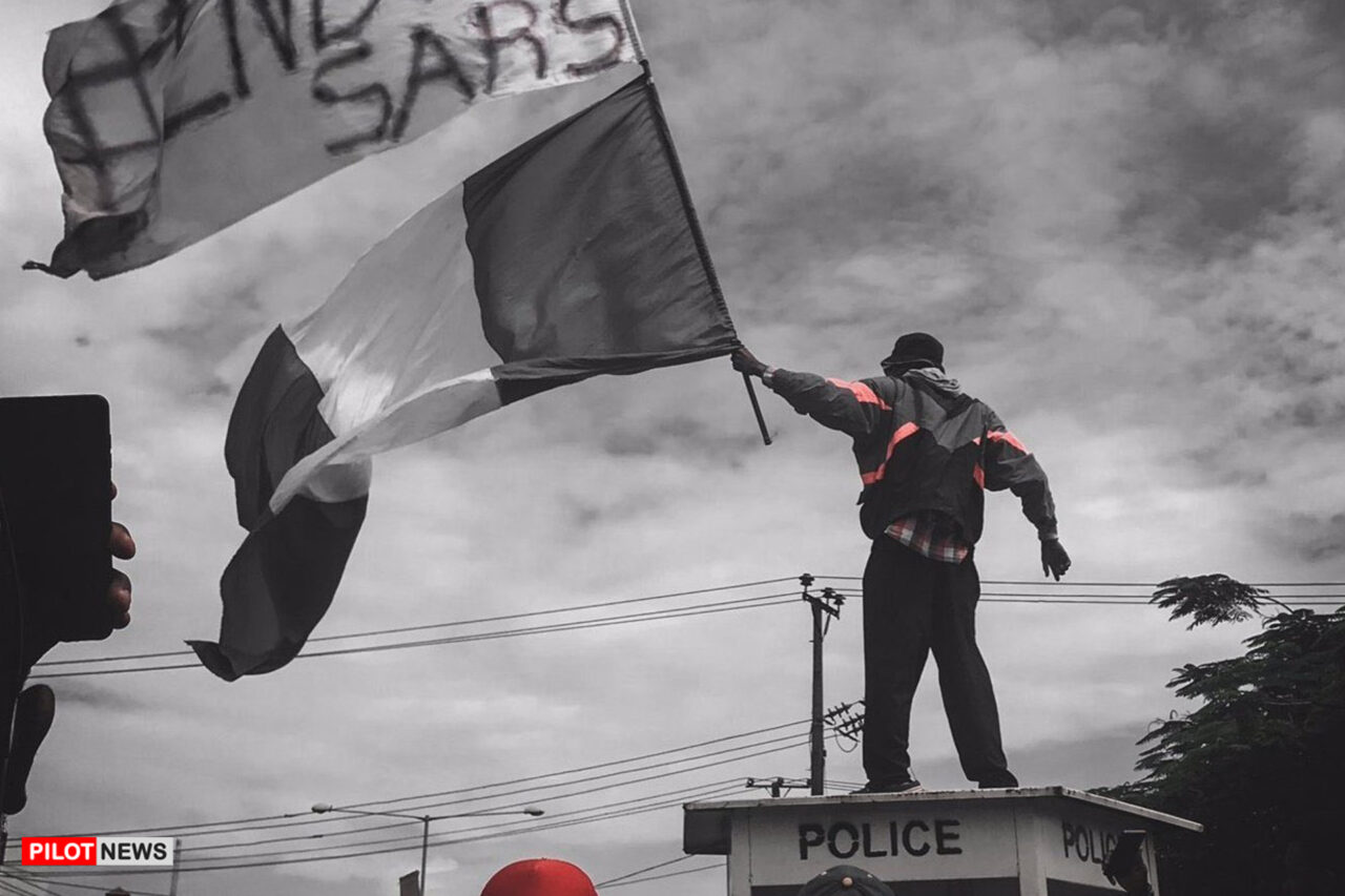 https://www.westafricanpilotnews.com/wp-content/uploads/2020/10/ENDSARS-A-protester-stands-atop-a-police-structure-in-Ikeja-capital-of-Lagos-state-during-EndSARS-demonstrations-on-October-11-2020.-Ayodeji-Adegoroye-10-17-20-1280x853.jpg